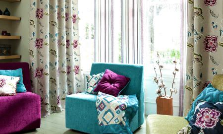 Prestigious Textiles -  Explore Fabric Collection - Bold modern colours - pink, green and turquoise blue lounge area with matching floral curtains and diamond design throw