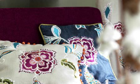 Prestigious Textiles -  Explore Fabric Collection - Navy blue and cream silk cushions with intricate floral designs and matching curtains