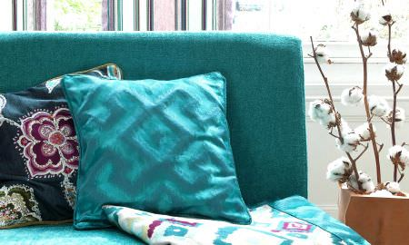 Prestigious Textiles -  Explore Fabric Collection - Bold turquoise armchair with matching cushion and diamond pattern throw in blue, pink and white