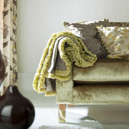 Prestigious Textiles -  Exquisite Fabric Collection - A classic couch upholstered in green reflective fabric with two cushions with a classic floral design and a light grey blanket
