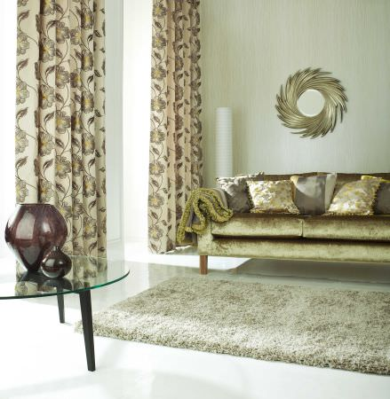 Prestigious Textiles -  Exquisite Fabric Collection - White curtains with with a gold and grey flower and vine grid and a classic upholstered couch with cushions for a classic modern setting