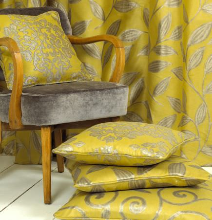 Prestigious Textiles -  Fairway Fabric Collection - Vivid yellow curtains and cushions decorated with classic leaves, flowers, and swirls, and a grey upholstered chair