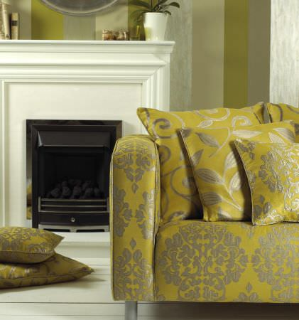 Prestigious Textiles -  Fairway Fabric Collection - A vivid yellow upholstered couch with a classic silver pattern, and yellow cushions with silver swirl and leaf designs