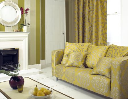 Prestigious Textiles -  Fairway Fabric Collection - Couch with yellow uphosltery with a classic pattern design, with cushions with swirls, and a yellow curtain with a leaf grid