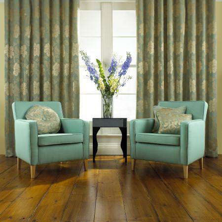 Prestigious Textiles -  Finesse Fabric Collection - Azure blue curtains with classic silver flower stitchings behind two light blue upholstered easy chairs with blue and silver cushions