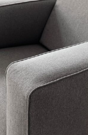 Prestigious Textiles -  Finlay Fabric Collection - A close-up shot of a modern upholstered armchair in grey without any additional decorative patterns