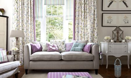 Prestigious Textiles -  Fiorella Fabric Collection - Contemporary living room, muted tans and whites with pink, teal detailing, striped cushions and tablecloth and floral curtains