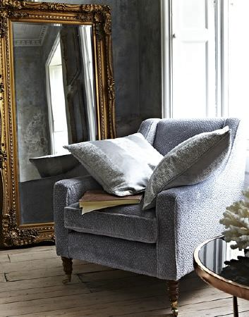 Prestigious Textiles -  Focus Fabric Collection - Modern dotted design on velvet armchair covered with two grey cushions featuring silky stripes