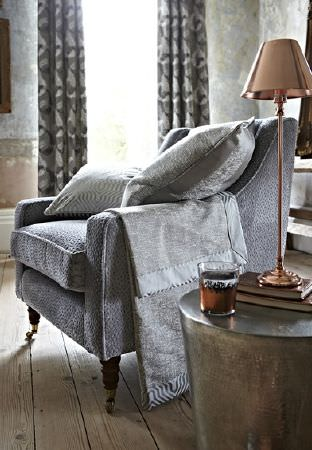 Prestigious Textiles -  Focus Fabric Collection - Elegant grey upholstered armchair covered with two luxurious cushions with modern designs in grey