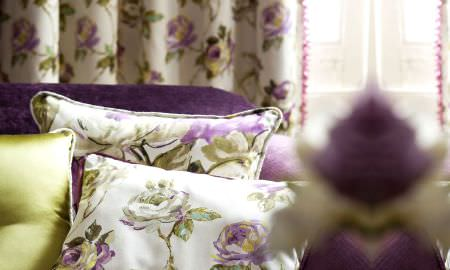 Prestigious Textiles -  Fragrant Harbour Fabric Collection - Modern living area - green and purple themed rose design curtains and sofa cushions