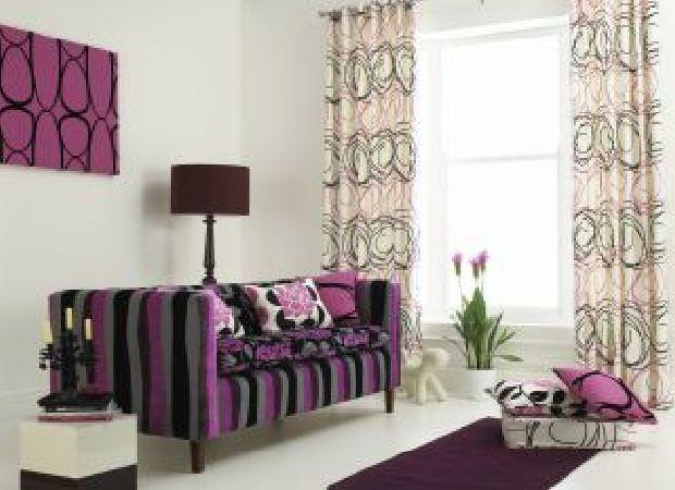 Prestigious Textiles -  Freedom Fabric Collection - Modern purple and black upholstered couch with floral pillows and white curtains with abstract decorative designs