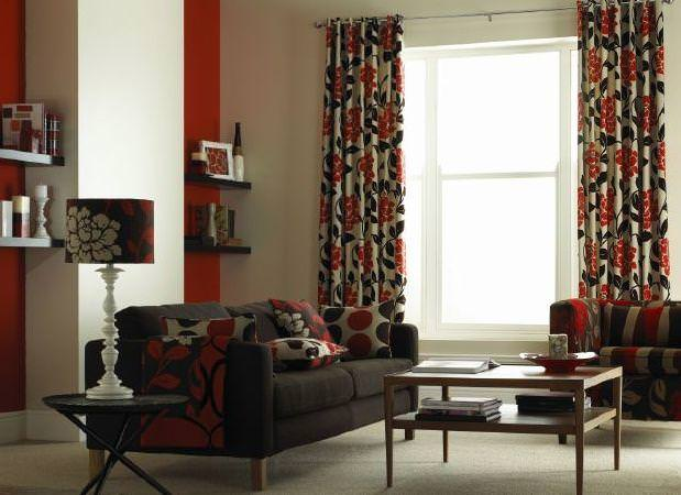 Prestigious Textiles -  Freedom Fabric Collection - White curtain and cushions with modern simple floral print, with a dark upholstered couch and a red floral lamp shade