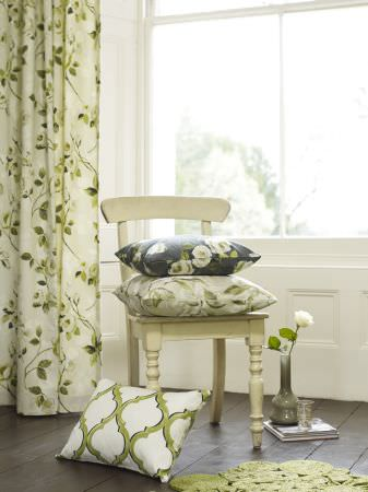 Prestigious Textiles -  Garden Party Fabric Collection - Classic white curtains with green leaf patterns and blue and white pillows with flowers and classic decorations