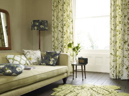 Prestigious Textiles -  Garden Party Fabric Collection - Classic white curtains with green leaves printed, a white upholstered couch, and white and blue flowery pillows