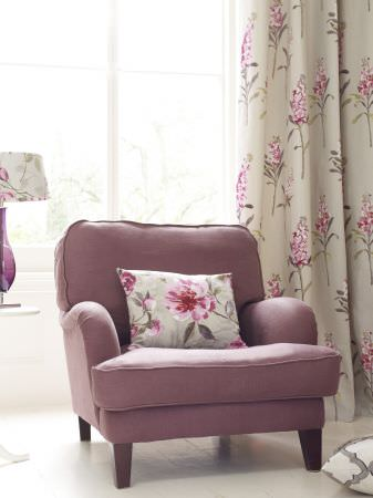 Prestigious Textiles -  Garden Party Fabric Collection - Faded purple upholstered easy chair with a pink flower printed cushion, and a light green curtain with pink lavender flowers