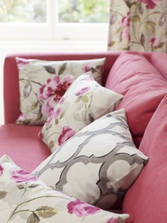 Prestigious Textiles -  Garden Party Fabric Collection - White cushions with pink roses and green leaves or classic patterns on a red upholstered couch