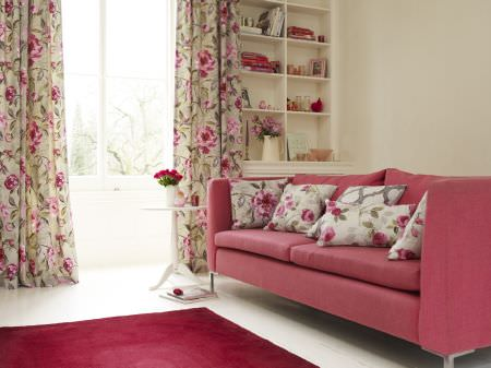 Prestigious Textiles -  Garden Party Fabric Collection - Red upholstered couch with white pillows with red roses, and a pale green curtain with pink roses and green leaf pattern for a modern room