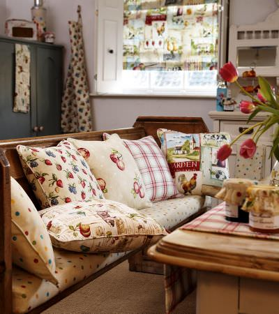 Prestigious Textiles -  Garden of England Fabric Collection - Roman Blinds with flowers, leaves and cockerels on neutral,  Seat cushions of cream with dots and cushions with floral and stripe patterns.