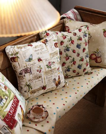 Prestigious Textiles -  Garden of England Fabric Collection - Church pew with cushion in light beige and multi-coloured dots; cushions with garden theme consisting of fruit and flowers.