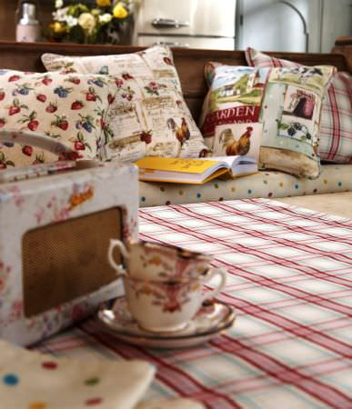 Prestigious Textiles -  Garden of England Fabric Collection - Seat cushion covered in light beige with multi-coloured dots; garden-theme cushions with patterns of fruit and flowers and check tablecloth.