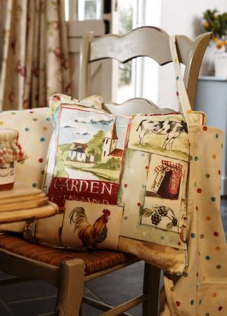 Prestigious Textiles -  Garden of England Fabric Collection - Taupe kitchen chair with garden/country theme cushionsin beige and red; beige  apron with multi-coloured dots.