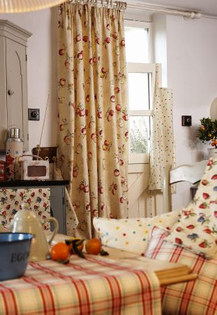 Prestigious Textiles -  Garden of England Fabric Collection - Beige curtains with red swirls, garden theme cushions with dots, fruit and red check with matching tablecloth.