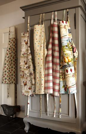 Prestigious Textiles -  Garden of England Fabric Collection - Taupe French-style cupboard with five aprons with patterns of fruit, dots, check and country scenes.