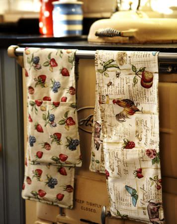 Prestigious Textiles -  Garden of England Fabric Collection - Aga-type stove with oven gloves with beige background wuth fruit, butterflies and cockerels.