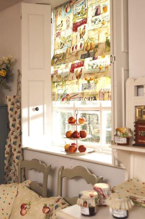 Prestigious Textiles -  Garden of England Fabric Collection - Light beige blinds with country-style pattern of fruit, flowers and cockerels; two taupe kitchen chairs with cushions with fruit and dots.