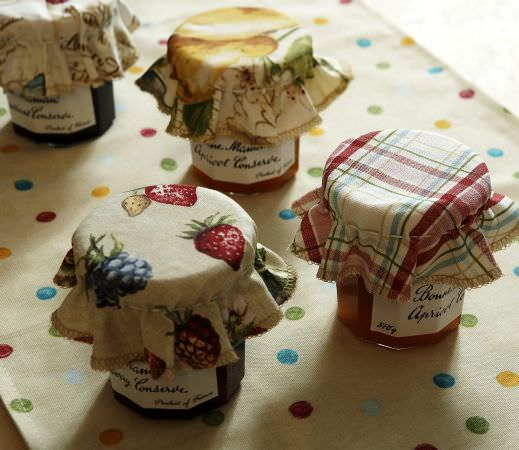 Prestigious Textiles -  Garden of England Fabric Collection - Four jam jar covers with fruit, floral and check pattern; Tablecloth in light beige with milti-coloured dots.