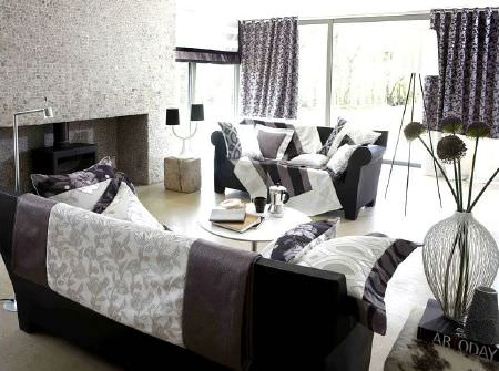 Prestigious Textiles -  Glamorous Fabric Collection - Black sofa with black and grey patterned curtains, cushions and blankets in black, white and grey, three lamps, grey strips made into a vase