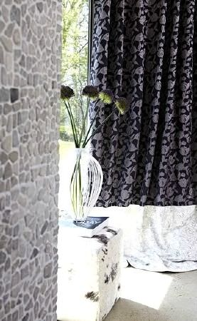 Prestigious Textiles -  Glamorous Fabric Collection - Grey mosaic wall, black curtains with a silver floral pattern, a white cube, and a vase which appears to be made of strips of white wicker