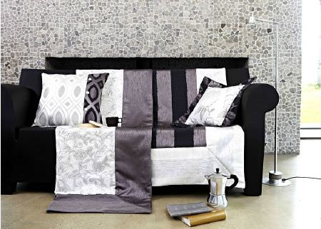 Prestigious Textiles -  Glamorous Fabric Collection - Black sofa in front of grey mosaic style wall, with black, white and grey cushions and blankets, a silver lamp and a silver cafetiere