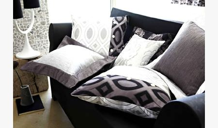 Prestigious Textiles -  Glamorous Fabric Collection - White, black and silver cushions scattered on a black sofa, beside a white lamp with two black lampshades, and a grey vase
