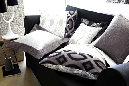 Prestigious Textiles -  Glamorous Fabric Collection - Silver, black and white cushions, plain black sofa, monochrome lamp with two shades, and a conical grey vase