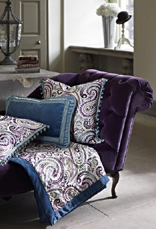Prestigious Textiles -  Grand Palais Fabric Collection - A Royal purple velvet chaise longue with plain and paisley patterned cushions and a throw made in white, blue and purple