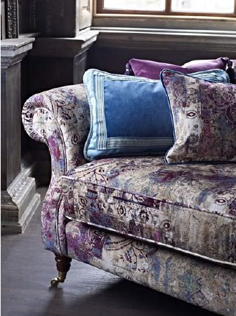 Prestigious Textiles -  Grand Palais Fabric Collection - A sofa covered with roughly printed fabric in purple and white shades, with patterned and plain blue and purple cushions