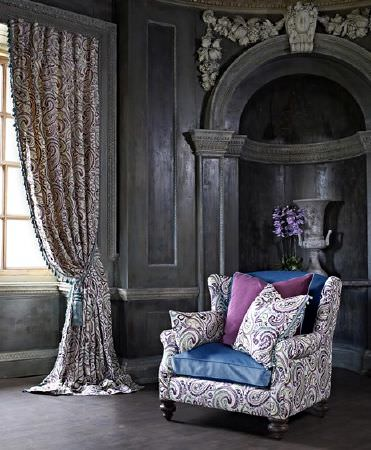 Prestigious Textiles -  Grand Palais Fabric Collection - Stylish paisley prints made in white, purple and blue, on curtains, an armchair and cushions, with blue and purple cushions