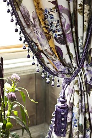 Prestigious Textiles -  Grand Palais Fabric Collection - Large florals in purple and dark grey on white curtains finished with a beaded trim and a dark purple tasselled tieback
