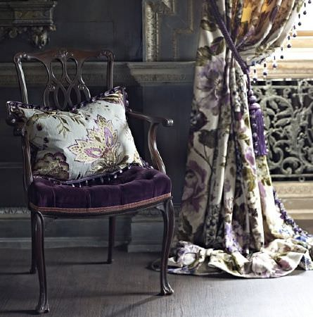 Prestigious Textiles -  Grand Palais Fabric Collection - An ornate black chair with a purple velvet seat cushion, a floral cushion, and purple, grey and white floral curtains
