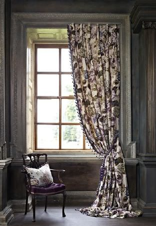 Prestigious Textiles -  Grand Palais Fabric Collection - A curtain with white, purple and grey florals, by a black chair with a velvet seat cushion and a patterned scatter cushion