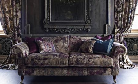 Prestigious Textiles -  Grand Palais Fabric Collection - A large sofa, cushions and curtains with florals and roughly printed patterns in dark shades of purple, grey and blue