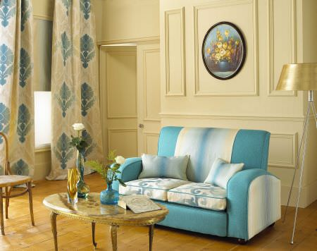 Prestigious Textiles -  Greek Mythology Fabric Collection - A teal upholstered couch with white bands and a classic pattern, and oyster white curtains with a classic blue design pattern