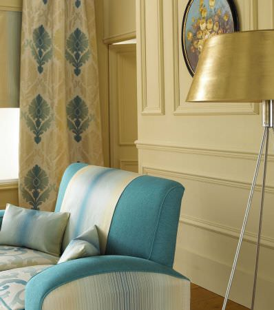 Prestigious Textiles -  Greek Mythology Fabric Collection - An oyster white curtain with teal blue and white decorative designs and a teal blue modern couch with white stripes and white pillows
