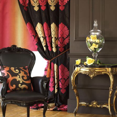 Prestigious Textiles -  Greek Mythology Fabric Collection - Antique black padded chair with a black cushion with a classic motif in vivid colours, and a black curtain with pink and yellow decorations