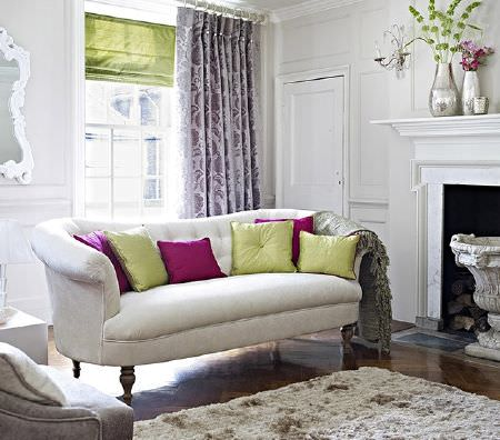 Prestigious Textiles -  Greenwich Fabric Collection - Large rounded white sofa, a grey armchair, fluffy rug, fuschia and lime cushions, purple and white curtains and a green blind