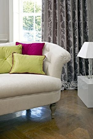 Prestigious Textiles -  Greenwich Fabric Collection - Fuschia and lime cushions on a white sofa with wood feet, with grey and white floral curtains, a white table and a lamp
