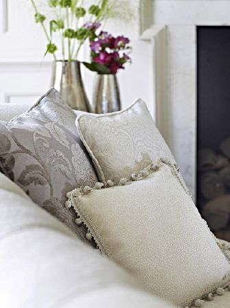 Prestigious Textiles -  Greenwich Fabric Collection - Pompom edging to one of three cream and grey patterned scatter cushions arranged on a white sofa, with chrome vases