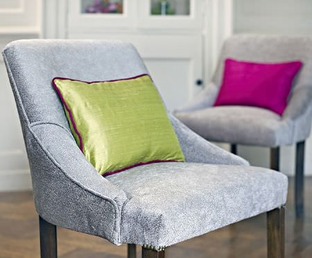 Prestigious Textiles -  Greenwich Fabric Collection - Two speckled grey and white armchairs with sloping armrests and dark wood legs, with a lime cushion and a fuschia cushion