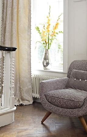 Prestigious Textiles -  Greenwich Fabric Collection - Stylish grey and white patterned armchair with wood legs, a plain grey cushion with white buttons and long cream curtains